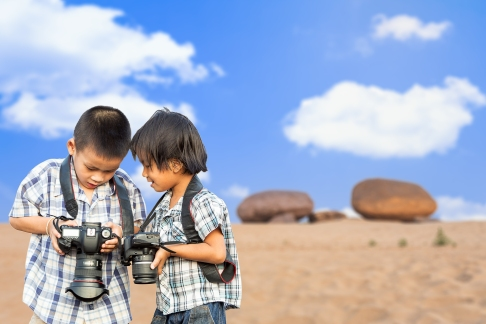 Asian child holding photo camera