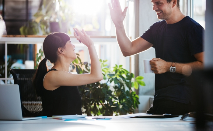 Successful business colleagues giving high five